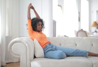 woman-in-orange-top-and-blue-denim-jeans-sitting-on-white-3961188